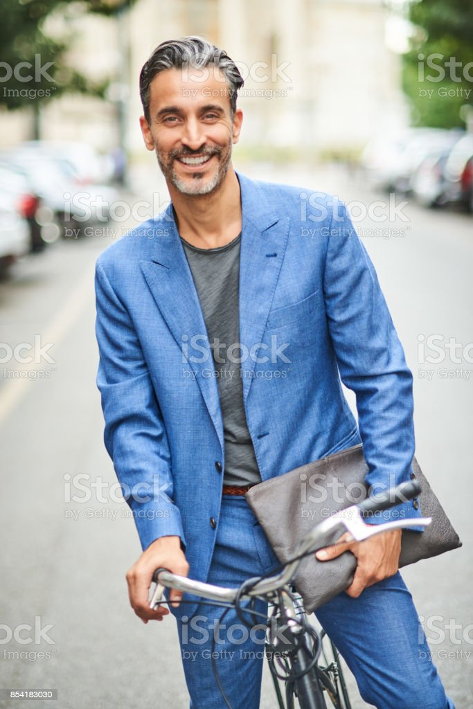 Portrait of handsome mature man on the bicycle. stock photo