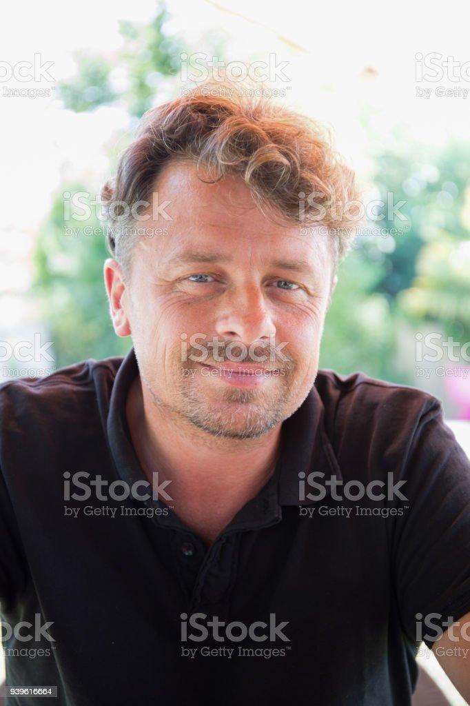 Portrait of handsome mature man outdoors garden home stock photo
