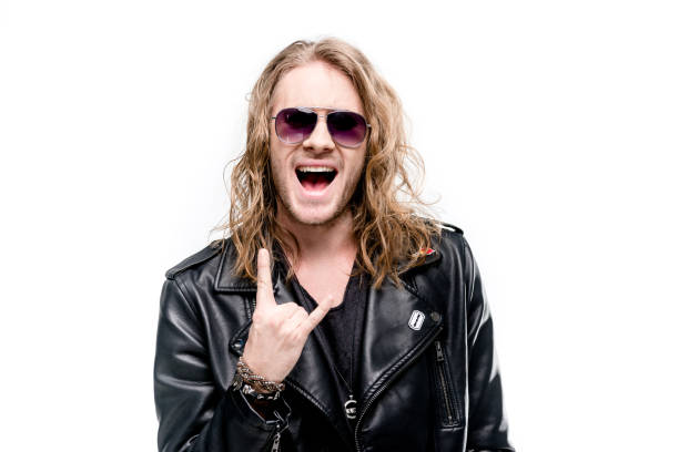 portrait of handsome rocker in black leather jacket and sunglasses showing rock sign isolated on white, rock star concept stock photo