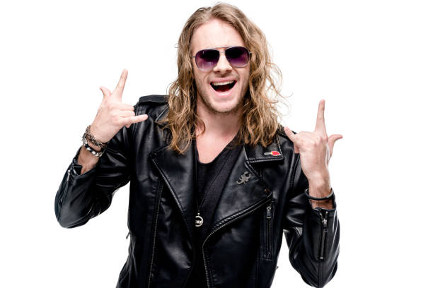 portrait of handsome rocker in black leather jacket and sunglasses showing rock signs isolated on white, rock star concept stock photo