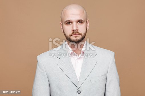 1162960006istockphoto Portrait of handsome sad despair middle aged bald bearded businessman in classic light gray suit standing, looking at camera with depressed face. 1026202382