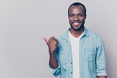 istock Portrait of handsome satisfied attractive cheerful joyful delightful afro guy dressed in casual clothing is showing aside on copyspace, isolated on grey background 925449552