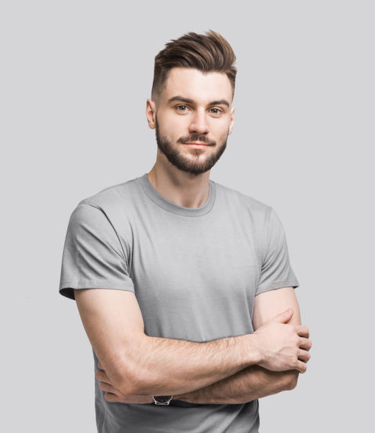 Portrait of handsome serious young man with crossed arms stock photo