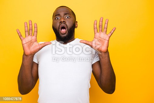 Portrait of handsome shocked scared punished man, showing two palms, opened mouth, isolated over bright vivid yellow background