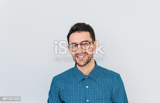 951331990 istock photo Portrait of handsome smart-looking smiling male posing for social advertisement wearing blue shirt and glasses, isolated on white background with copy space for your promotional information or content 951331020