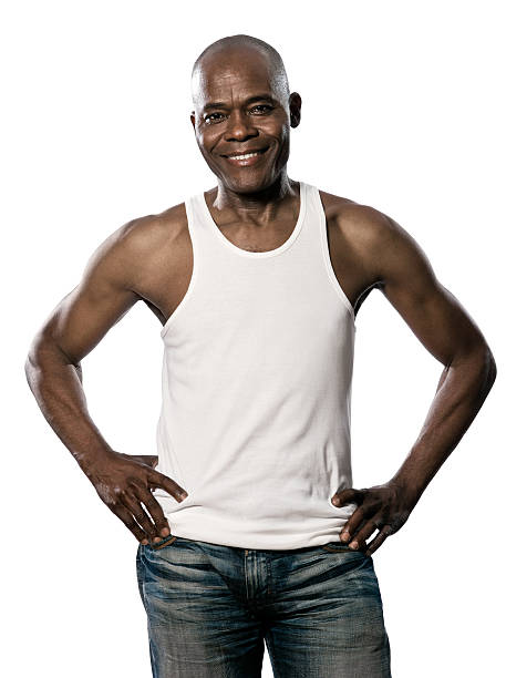 Portrait of handsome smiling african man with hands on waist Portrait of a happy african afro american african man with hands on hips jeans and sleeveless t-shirt standing in studio    on white background akimbo stock pictures, royalty-free photos & images