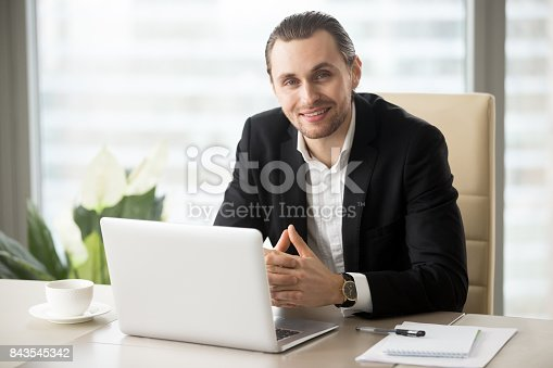 istock Portrait of handsome smiling businessman in suit in the office. 843545342