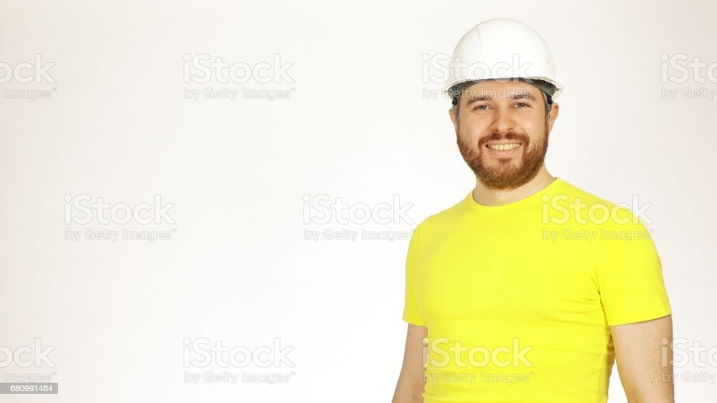 Portrait of handsome smiling construction engineer or architect in yellow tshirt and hard hat against white background royalty-free stock photo