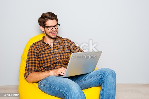 istock Portrait of handsome smiling man in glasses working on laptop 947303582