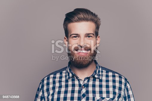 636829368istockphoto portrait of handsome smiling young man looking at camera isolatet on gray wall 948743568