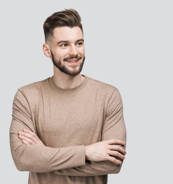 Portrait of handsome smiling young man looking up stock photo