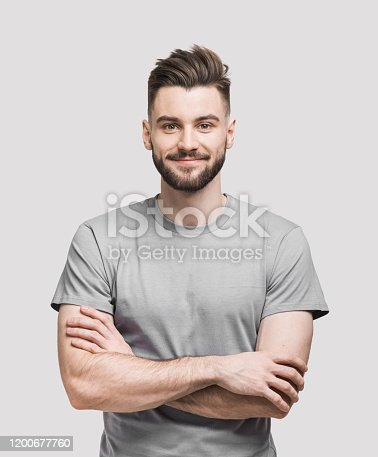 Cheerful young man with crossed hands looking to the camera. Isolated on gray background