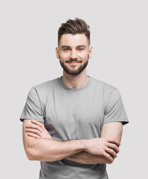 Portrait of handsome smiling young man with crossed arms stock photo