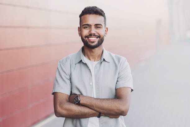 Portrait of handsome smiling young man with folded arms in a city stock photo