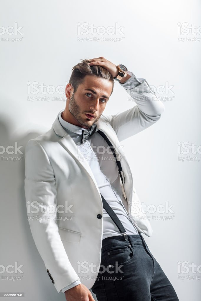 Portrait of handsome stylish man leaning at wall stock photo