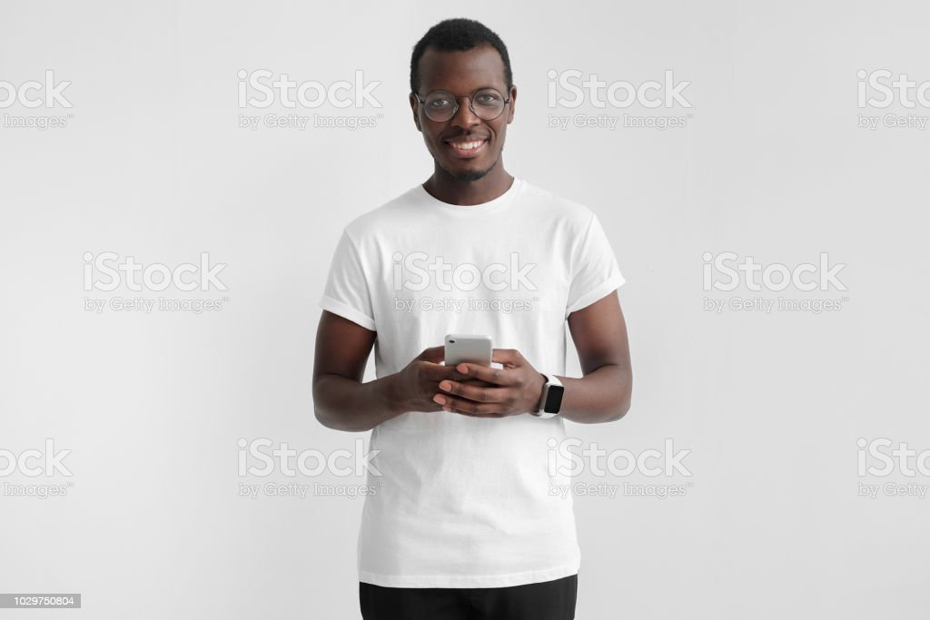 Portrait of handsome young african american man in white t-shirt, holding smartphone, looking at camera and laughing, isolated on gray background stock photo