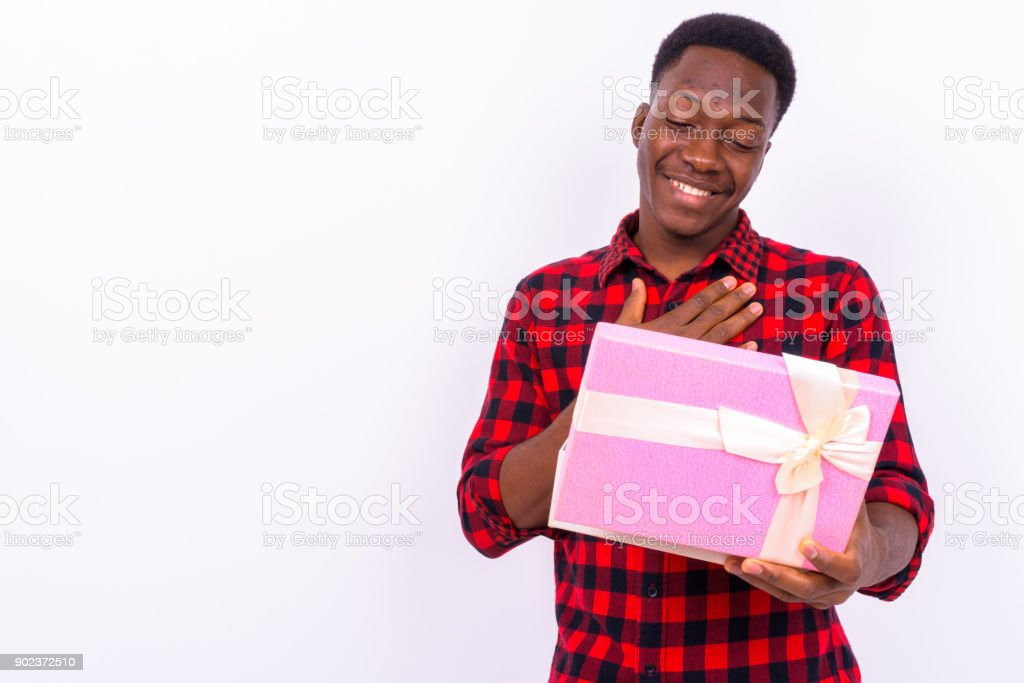 Portrait Of Handsome Young African Man Holding Gift Box Against White Background stock photo