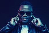 istock Portrait of handsome young african man listening music with wireless earphones 1153003865