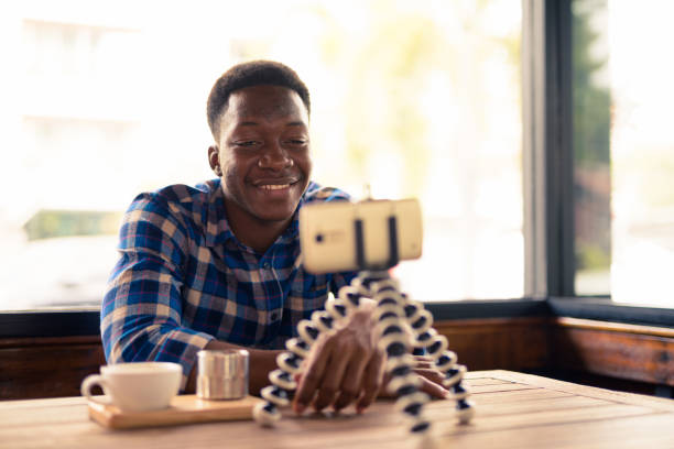 Portrait Of Handsome Young African Man Sitting In Coffee Shop stock photo