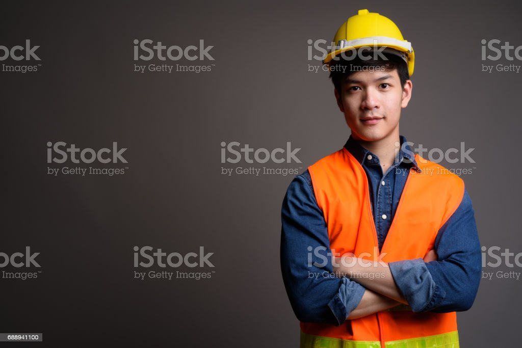 Portrait of handsome young Asian man wearing hard hat stock photo