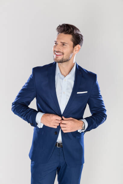 Portrait of handsome young businessman Portrait of handsome young businessman standing over gray background and looking away smart casual stock pictures, royalty-free photos & images