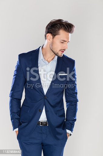 Portrait of handsome young businessman standing with his hands in pocket and looking down against gray background