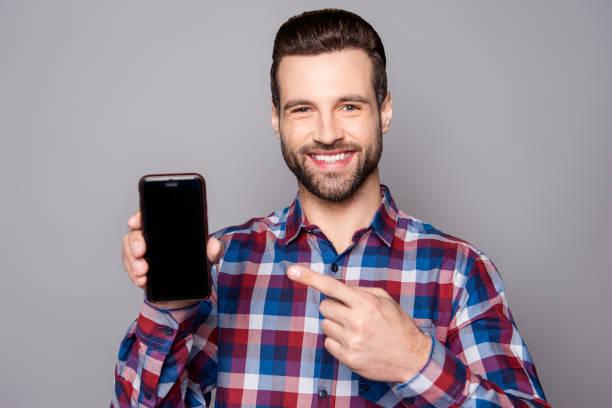 彼のスマート フォンの黒いスクリーンを示すハンサムな青年実業家の肖像画 ストックフォト
