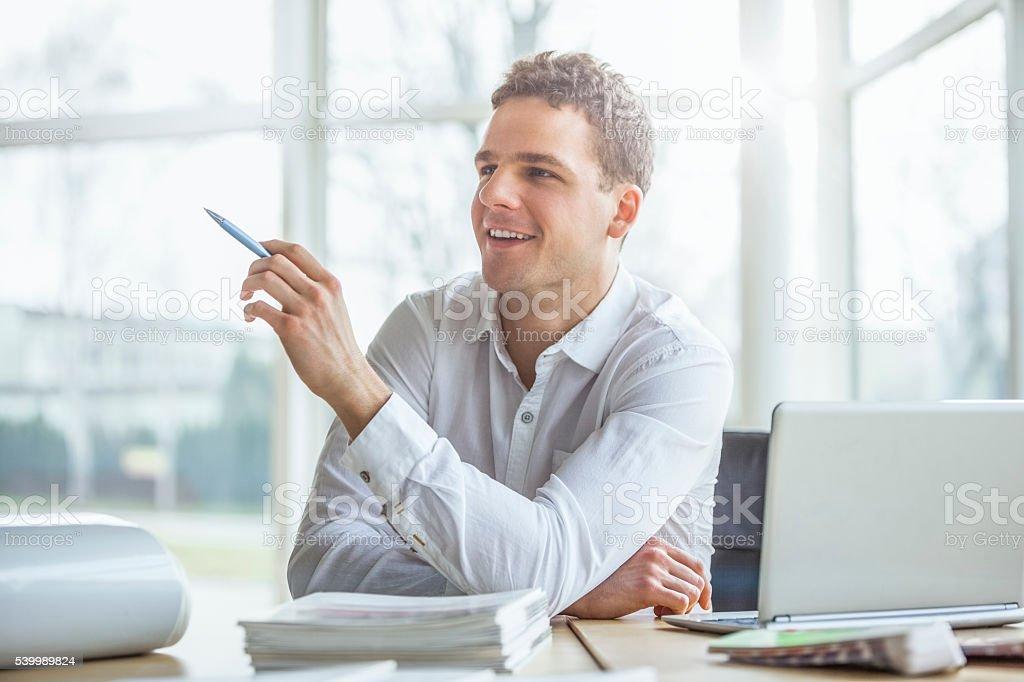 Porträt von attraktivem jungen Geschäftsmann benutzt Laptop am Schreibtisch – Foto