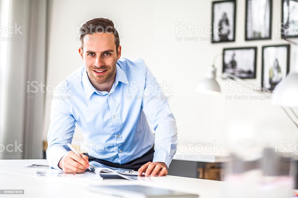 Portrait of handsome young businessman working at desk in office – Foto