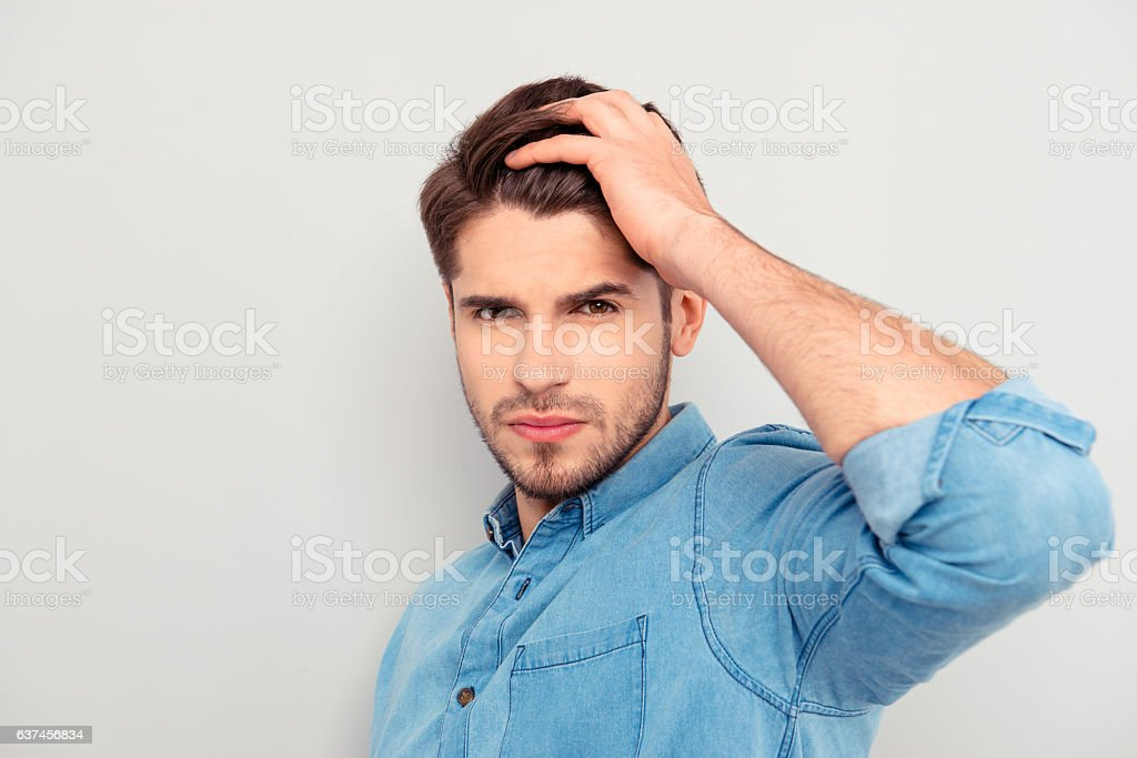 Portrait of handsome young guy combing his hair with fingers stock photo