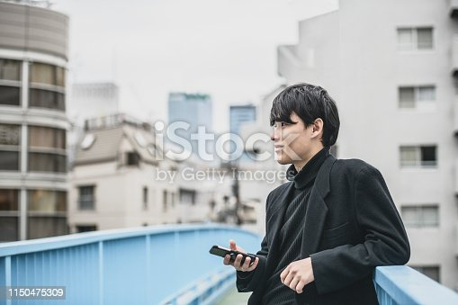Young Asian man wearing black clothes on bridge in urban scene, with smartphone, looking away