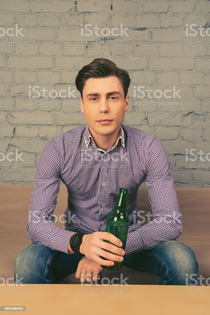 Portrait of handsome young man holding bottle of beer and watching tv royalty-free stock photo