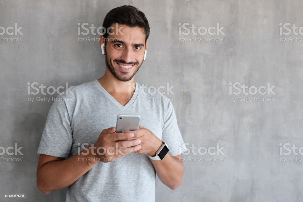 Portrait of handsome young man in gray t-shirt, holding smartphone, looking at camera and smiling, standing against textured wall with copy space for your ads stock photo
