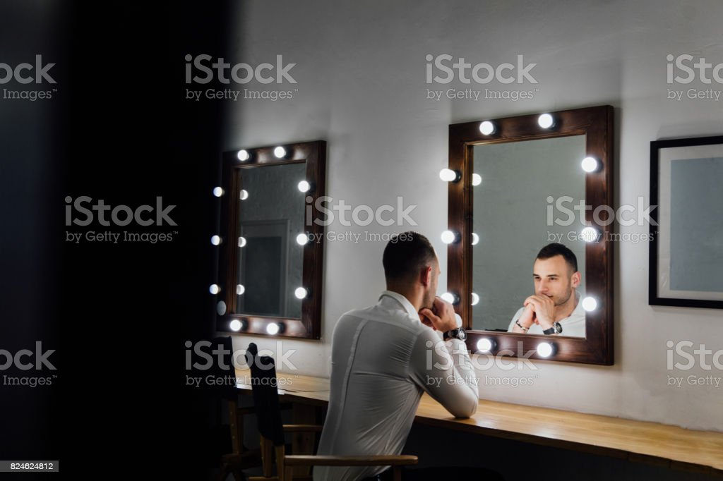 Portrait of handsome young man in white shirt looking into the mirror stock photo