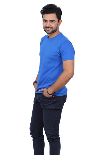 Portrait of handsome young man on white background. He is wearing blue t-shirt. Male is standing with hands in pockets.