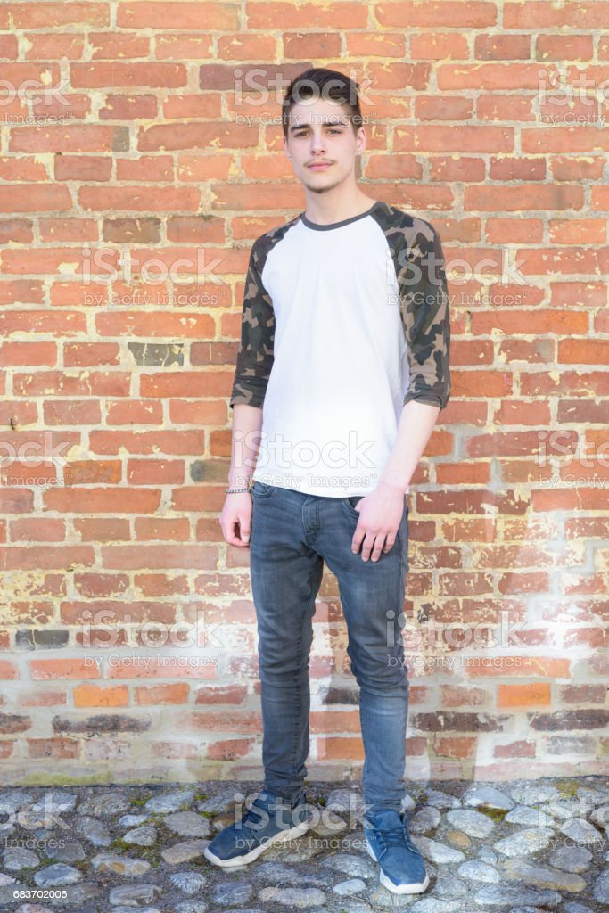 Portrait of handsome young man outdoors against brick wall stock photo