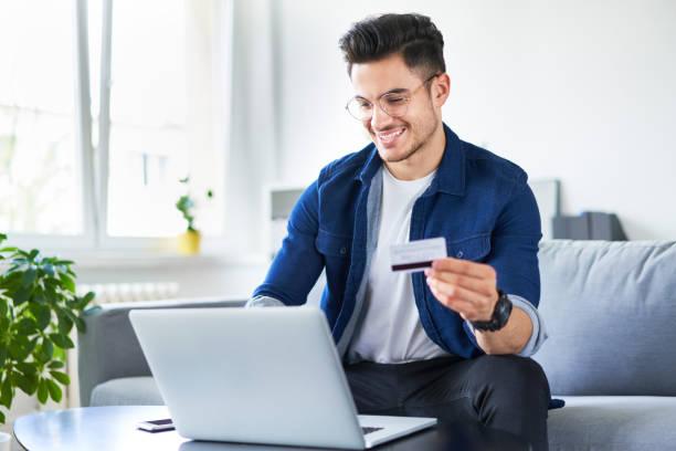 Porträt eines hübschen jungen Mannes, der online mit Kreditkarte und Laptop bezahlt, während er zu Hause sitzt – Foto