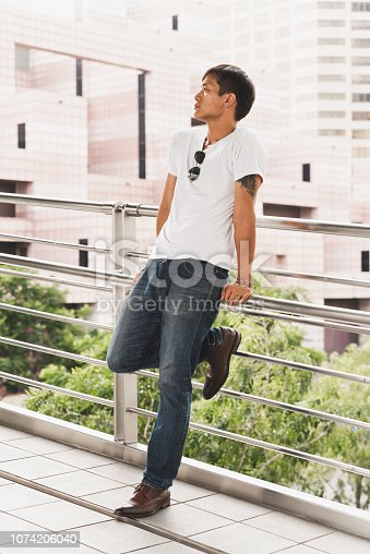 Asian Close-up of confident male is wearing t-shirt. Standing on bridge with building background.