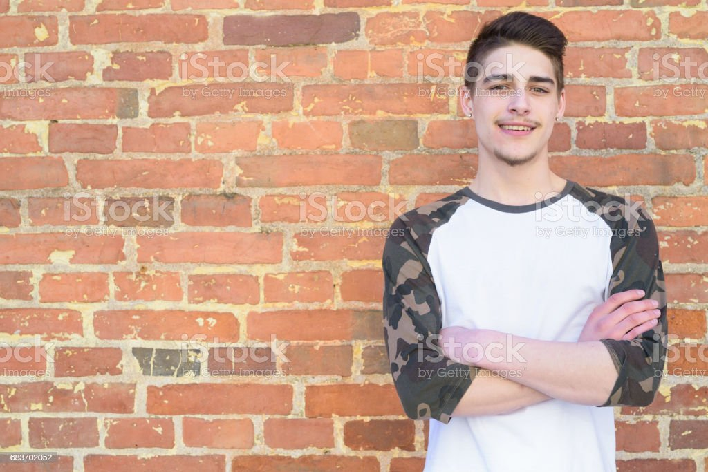 Portrait of handsome young man smiling with arms crossed outdoors against brick wall stock photo