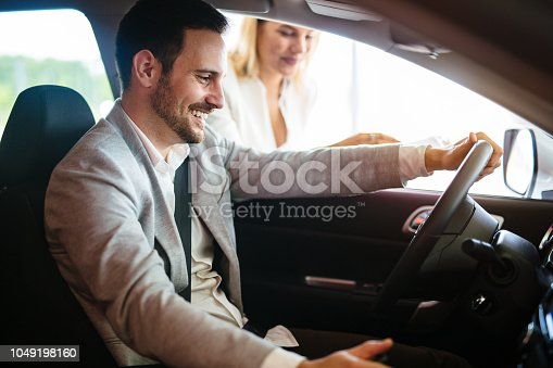 939005154 istock photo Portrait of handsome young man taking luxury car for test drive, sitting inside and smiling 1049198160