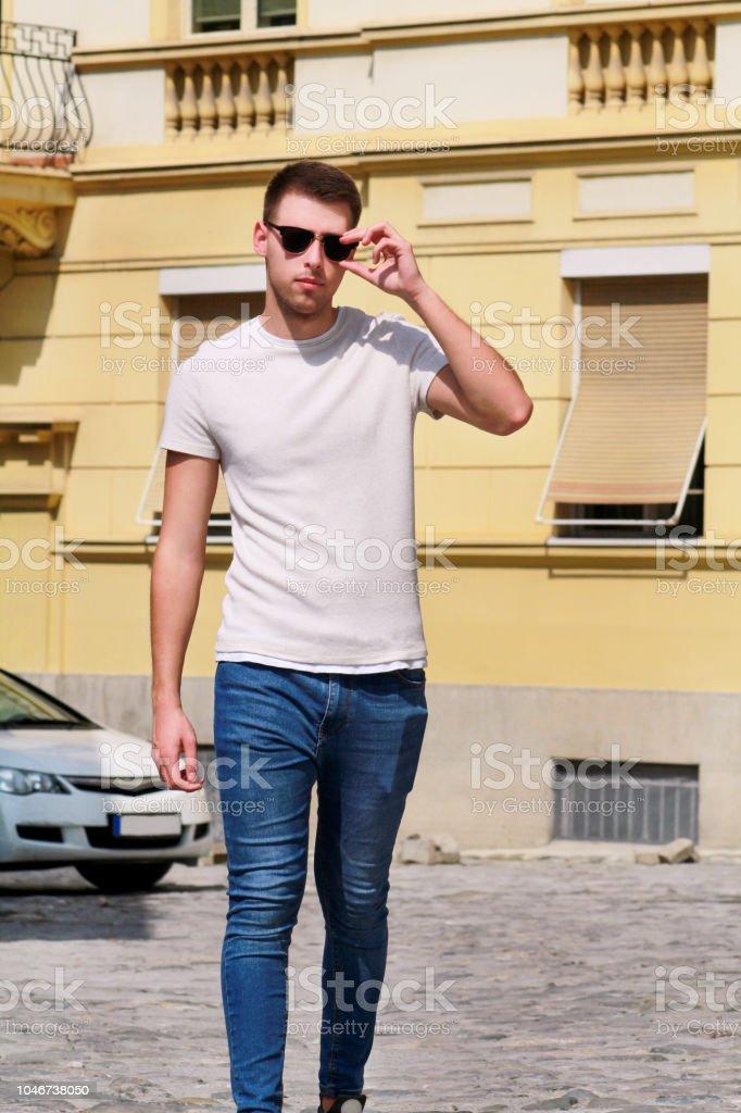 Retrato de jovem bonito com óculos de sol é posar e andando na rua urbana da cidade. Modelo masculino-fotos ao ar livre, rapaz da moda urbana, cara elegante, estilo de vida hippie. White t-shirt e jeans. - foto de acervo