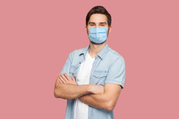 Portrait of handsome young man with surgical medical mask in blue casual style shirt standing, raised arms and looking at camera with smile. stock photo