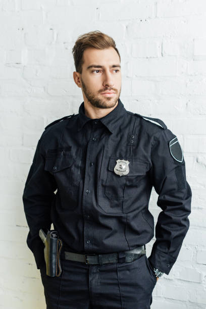 portrait of handsome young policeman in front of white brick wall portrait of handsome young policeman in front of white brick wall police uniform stock pictures, royalty-free photos & images