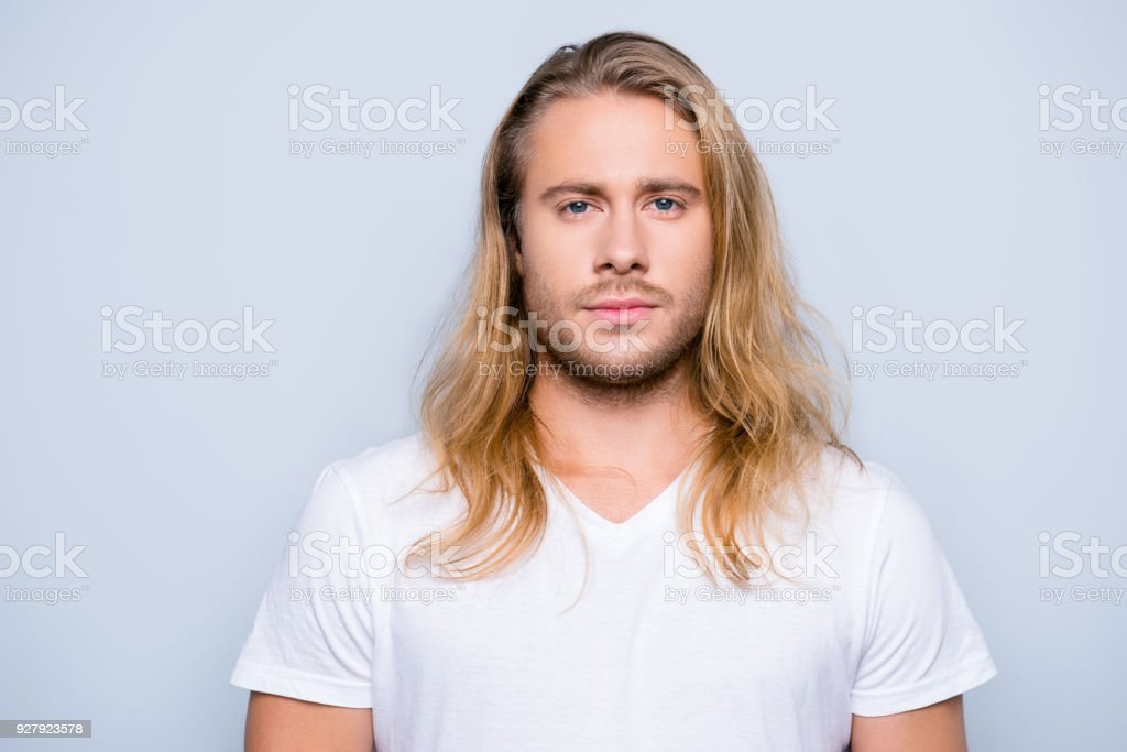 Portrait of handsome young serious confident young guy with blonde long hair in white tshirt, isolated on grey background - foto stock