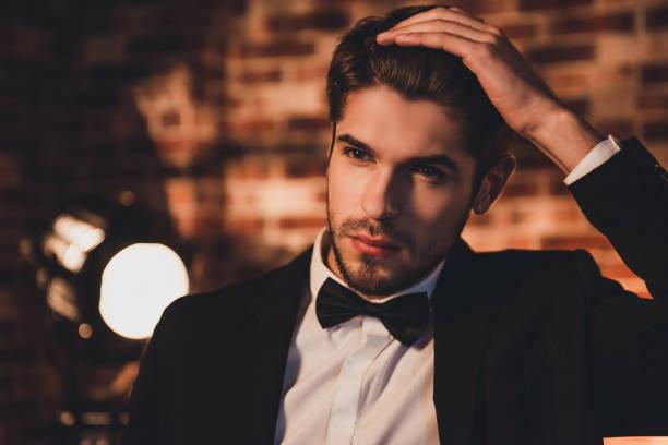 porträt der hübsche junge sexy bräutigam seine haare zu berühren - bräutigam anzug vintage stock-fotos und bilder