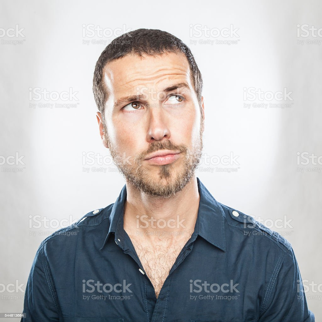 Portrait of handsome young thoughtful man isolated over white ba stock photo