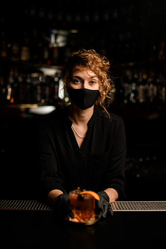 portrait of handsome young woman in black mask and black gloves who stands behind the bar and holds glass with cocktail