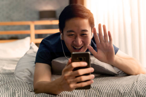 Portrait of happy 30s aged Asian man in casual clothing making facetime video calling with smartphone at home. He's waving at people on phone screen.