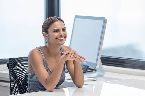 Portrait of happy Aboriginal Australian businesswoman sitting at desk stock photo