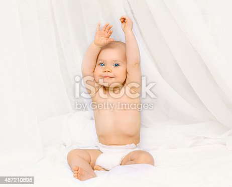 1084486306 istock photo Portrait of happy active baby in diapers playing on bed 487210898